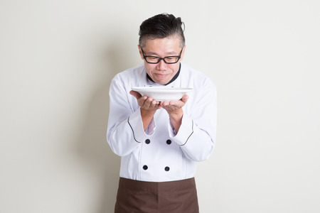 aromas: Portrait of 50s mature Asian male chef in uniform presenting dish and smelling the aroma, empty plate ready for food, standing on plain background with shadow, copy space.