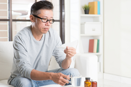 Portrait of casual 50s mature Asian man back pain, pressing on hip with painful expression, sitting on sofa at home, medicines and water on table. Standard-Bild