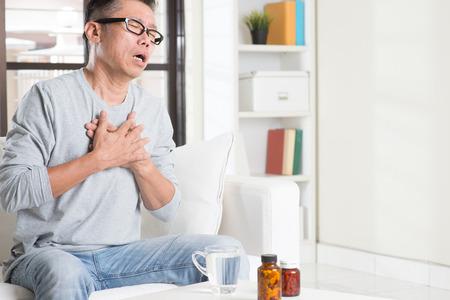 Volwassen 50s Aziatische man hartzeer, te drukken op de borst met pijnlijke uitdrukking, zittend op de bank thuis, geneesmiddelen op tafel.