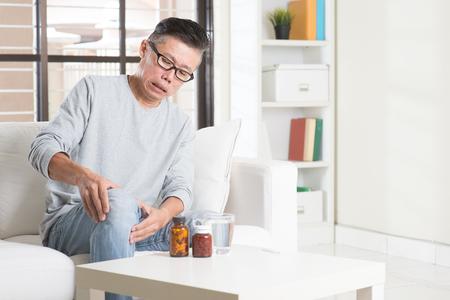 de rodillas: Retrato de 50s madura casual dolor Asia hombre de la rodilla, presionando sobre articulación de la rodilla con la expresión dolorosa, sentado en el sofá en casa, medicinas y agua en la mesa. Foto de archivo