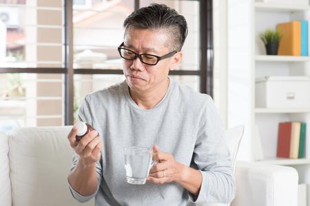 Men health concept. Portrait of 50s mature Asian man reading the label on bottle medicine, sitting on sofa at home. Banque d'images