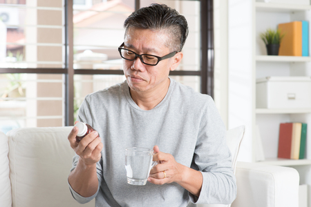 Men health concept. Portrait of 50s mature Asian man reading the label on bottle medicine, sitting on sofa at home. Standard-Bild