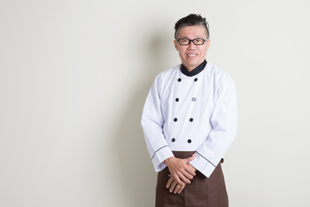 Portrait of 50s mature Asian male chef in uniform smiling, standing on plain background with shadow, copy space. Stock Photo