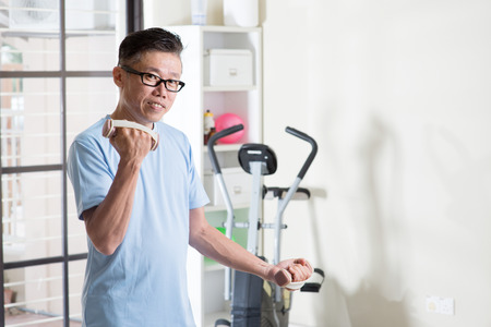 Portrait of active 50s mature Asian man in sportswear doing weight lifting dumbbells exercise, workout at indoor gym room.