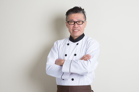 Portrait of confident 50s mature Asian male chef in uniform arms crossed, standing on plain background with shadow, copy space.
