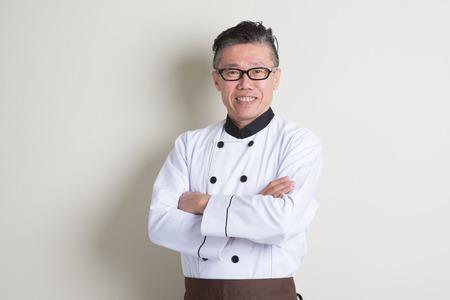 Portret van vertrouwen jaren '50 volwassen Aziatische mannelijke chef-kok in uniform gekruiste armen, staande op duidelijke achtergrond met schaduw, kopie ruimte. Stockfoto - 46958048
