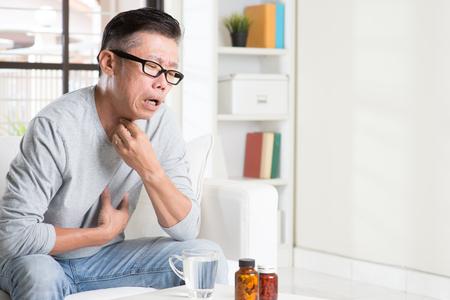 カジュアルな 50 代中年のアジア人苦しい表情と喉の痛み、喉、屋内家庭生活のライフ スタイルをクリアの首に手します。