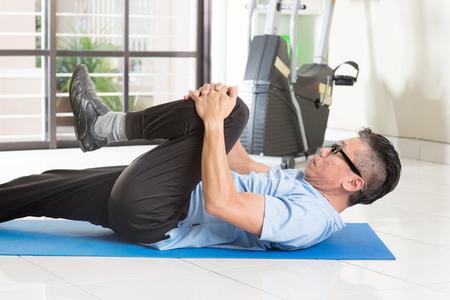 Portret van actieve jaren '50 volwassen Aziatische man in sportkleding doet been stretching op oefening mat, training bij indoor fitnessruimte. Stockfoto