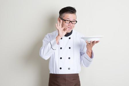 Oudere Aziatische chef-kok met een lege plaat, waaruit blijkt lekker en tevreden handteken, staand op een effen achtergrond.