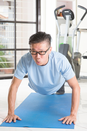 pushup: Portrait of active 50s mature Asian man in sportswear doing pushup on exercise mat, workout at indoor gym room. Stock Photo