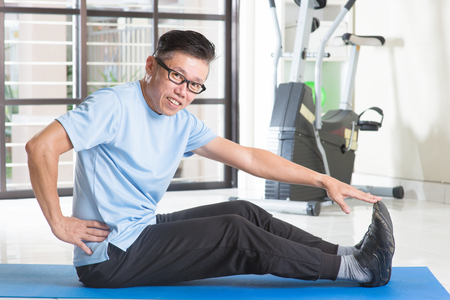 50s: Portrait of sporty 50s mature Asian man in sportswear doing leg stretching on exercise mat, workout at indoor gym room.