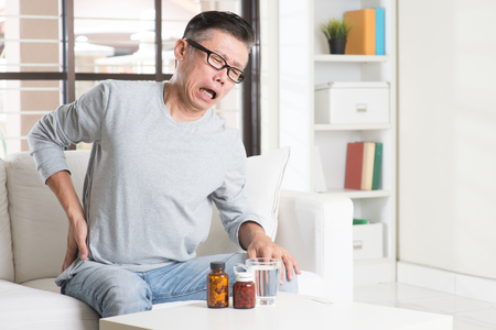 Portrait of casual 50s mature Asian man back pain, pressing on hip with painful expression, sitting on sofa at home, medicines and water on table. Stockfoto