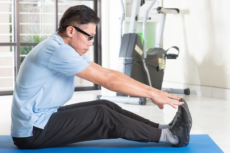 senior exercising: Portrait of 50s mature Asian man in sportswear doing leg stretching on exercise mat, workout at indoor gym room. Stock Photo