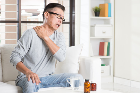 Portrait of casual 50s mature Asian man shoulder pain, pressing on neck with painful expression, sitting on sofa at home, medicines and water on table.
