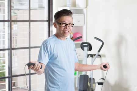 50s: Portrait of active 50s mature Asian man in sportswear doing rope skipping exercise, workout at indoor gym room.