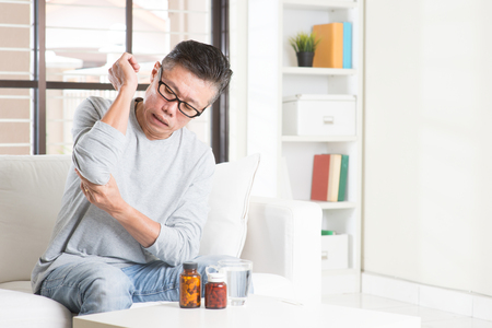 elbow pain: Portrait of casual 50s mature Asian man elbow pain, pressing on elbow joint with painful expression, sitting on sofa at home, medicines and water on table. Stock Photo