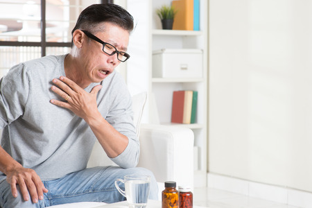 Portrait of casual 50s mature Asian man coughing, pressing on chest with painful expression, sitting on sofa at home, medicines and water on table.