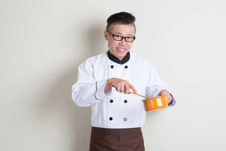 Portrait of mature Asian male chef in uniform cooking food, standing on plain background with shadow, copy space on side.