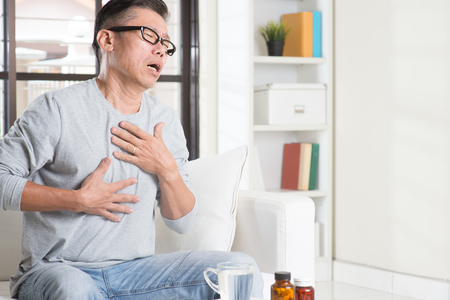 Portrait of casual 50s mature Asian man heartburn, pressing on chest with painful expression, sitting on sofa at home, medicines and water on table. Stockfoto