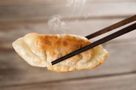 Close up fresh pan fried dumpling with chopsticks. Chinese food with hot steams on rustic vintage wooden background.