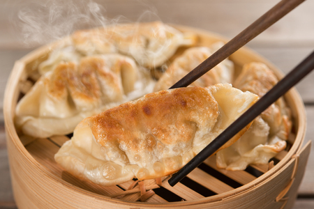 gyoza: Fresh pan fried dumpling on bamboo basket with chopsticks. Chinese food with hot steams on rustic vintage wooden background.