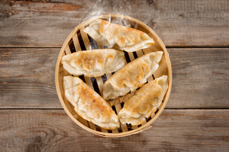 basket: Top view fresh pan fried dumpling on bamboo basket. Chinese food with hot steams on rustic vintage wooden background. Stock Photo