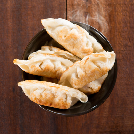 gyoza: Top view fresh pan fried dumplings on bowl. Chinese dish with hot steams on rustic vintage wooden background. Stock Photo
