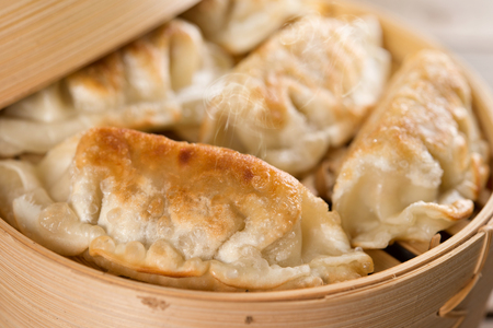 food basket: Close up fresh pan fried dumpling on bamboo basket. Chinese food with hot steams on rustic vintage wooden background. Stock Photo