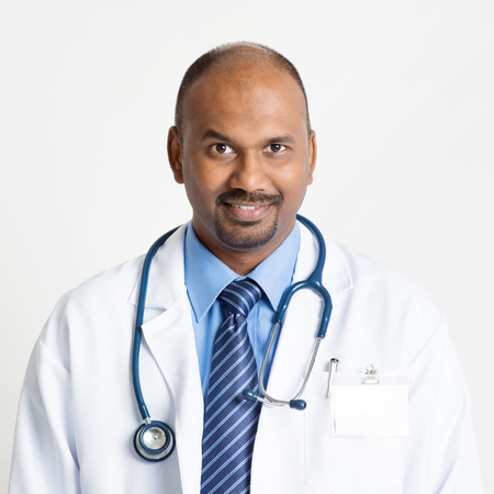Portrait of mature Indian male medical doctor in uniform smiling, standing on plain background with shadow.