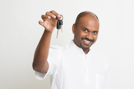 white car: Mature Asian Indian estate agent or salesman showing a key, India male business man, standing on plain background with shadow.