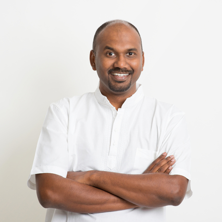 shadow man: Portrait of mature casual business Indian man arms crossed and smiling, standing on plain background with shadow.