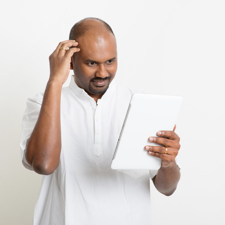 Portrait of mature Indian man headache while reading on digital tablet computer, on plain background with shadow.