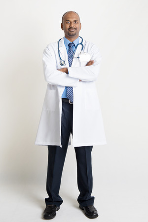 pakistani ethnicity: Full length confident mature Indian male medical doctor in uniform looking at camera, standing on plain background with shadow. Stock Photo