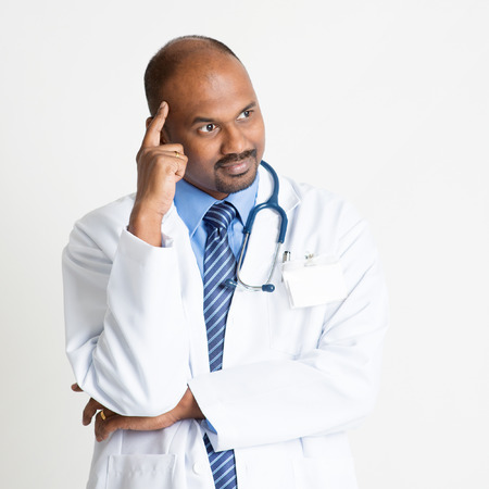 pakistani ethnicity: Portrait of mature Indian male medical doctor in uniform thinking, standing on plain background with shadow.