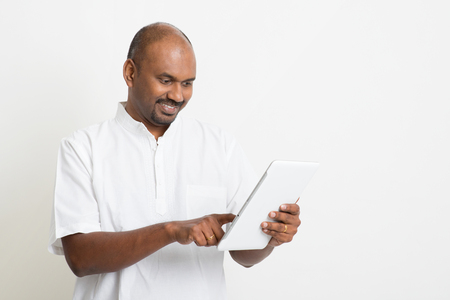 casual business man: Portrait of mature casual business Indian man using digital tablet pc, standing on plain background with shadow. Stock Photo