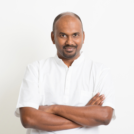 Portrait of mature casual business Indian man arms crossed, standing on plain background with shadow.
