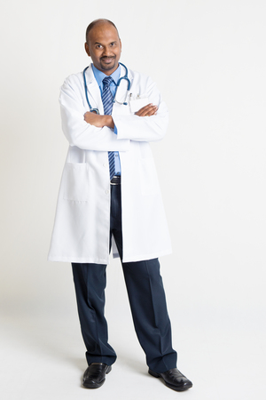 pakistani ethnicity: Full length mature Indian male medical doctor in uniform arms crossed standing on plain background with shadow.