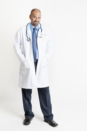 Full length confident mature Indian male medical doctor in uniform standing on plain background with shadow.