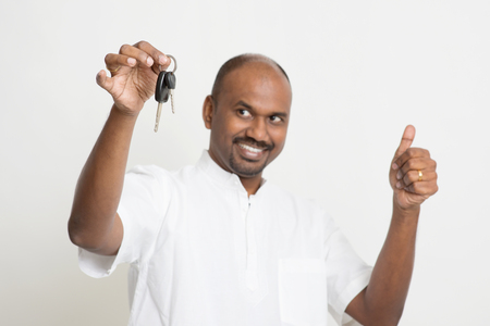 key handover: Portrait of Indian man holding new house key and thumb up, real estate property agent concept, focus on key, standing on plain background with shadow.