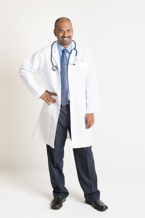 pakistani ethnicity: Full length mature Indian male medical doctor in uniform standing on plain background with shadow.