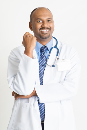 pakistani ethnicity: Portrait of happy mature Indian male medical doctor in uniform smiling, standing on plain background with shadow.