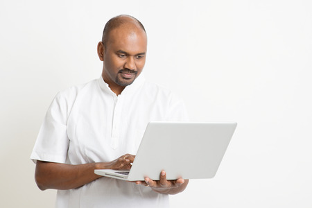 man with laptop: Portrait of mature casual business Indian man using laptop computer, standing on plain background with shadow.