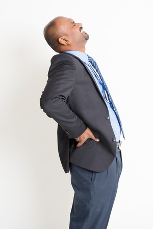 backpain: Indian businessman backache, holding his spine with painful face expression, standing on plain background.