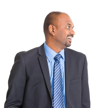ethnicity: Portrait of mature Indian businessman smiling and looking to side, standing on plain background.