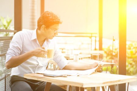 daily newspaper: Asian Indian business man reading newspaper while drinking a cup hot milk tea at cafeteria, with beautiful golden sunlight. Stock Photo