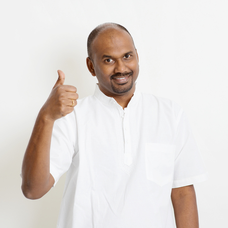 Portrait of happy mature casual business Indian man thumb up, standing on plain background with shadow. Stock Photo