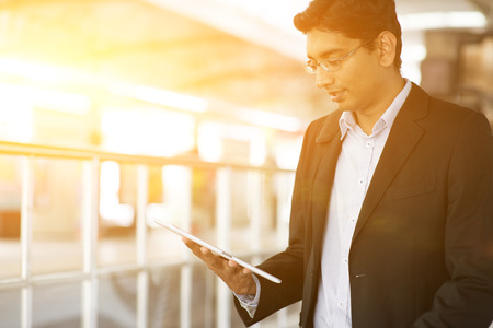 tablet: Indian business man using tablet computer while waiting train at railway station, beautiful golden sunset background. Stock Photo