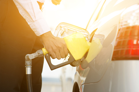refilling: Close up business man pumping gasoline fuel in car at gas station, golden sunlight background.