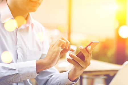 EMPRESARIO: hombre de negocios indio que usa smartphone en la cafetería al aire libre, hermosa luz del sol de oro borrosa en la parte posterior.