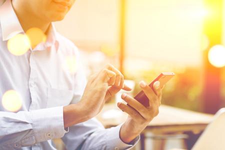 Homme d'affaires indien utilisez un Smartphone à la cafétéria en plein air, belle lumière dorée du soleil floue à l'arrière. Banque d'images